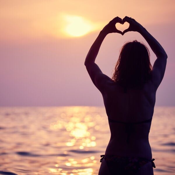 Heart shape made with hands, morning sun in the horizon. Heart against beautiful sunset.